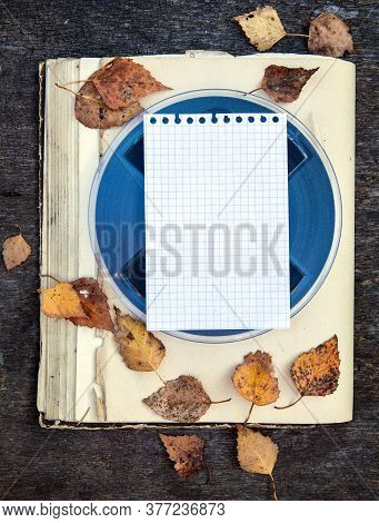 Empty Paper On The Vintage Reel With A Tape And Autumnal Leaves On The Old Book Closeup