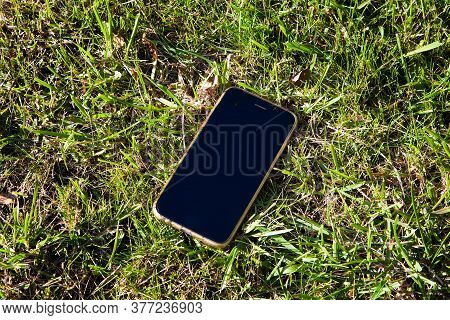 Lost Mobile Phone On The Grass In The Park