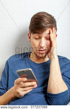 Unhappy Young Man With A Phone By The Wall At The Home