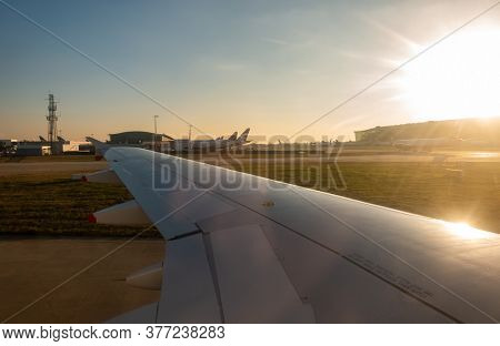 HEATHROW AIRPORT, LONDON, ENGLAND January 20 2019, view across the wing of a British Airways aircraft landing and airplanes waiting at sunset, Terminal 5, Heathrow Airport, London, England