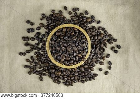 Coffee Beans On Wooden Bowl Isolated Top Viwe On Sackcloth Background.