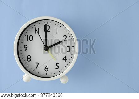 The Clock Is Clockwise White At 14 O'clock Or 2 O'clock. Top View In Blue Background. Clipping Path.