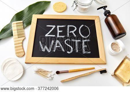 beauty, sustainability and eco living concept - natural cosmetics, bodycare eco products and chalkboard with zero waste words or lettering on white background