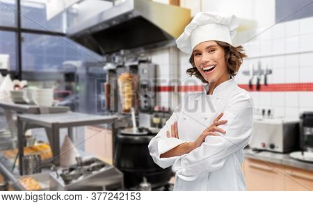 cooking, culinary and people concept - happy smiling female chef in toque with crossed arms over restaurant or kebab shop kitchen background