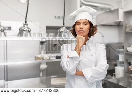 cooking, culinary and people concept - female chef in toque thinking over restaurant kitchen background