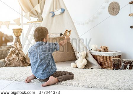 Back view of little boy shooting paper target with slingshot sitting on floor in kids room