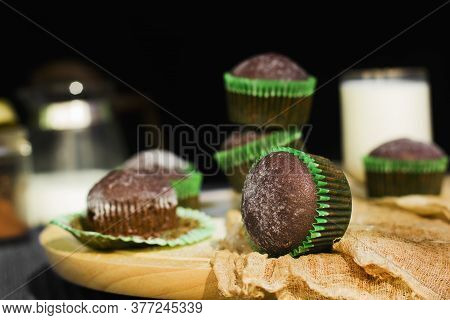 Chocolate Muffins On A Dark Background. Powdered Sugar Muffins. Cupcakes With Milk. Bakery Products.