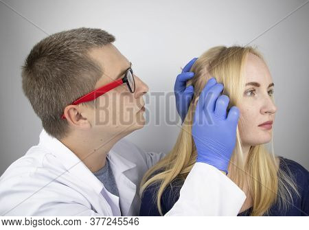 A Doctor Trichologist Conducts A Study Of The Hair Of A Blonde. Alopecia Treatment. Hair Loss, Alope
