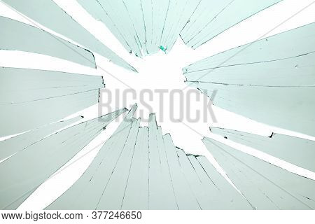 Closeup Of Broken And Cracked Glass With Hole On A White Background