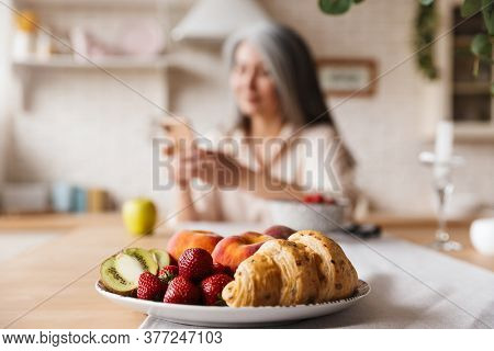 Image of unfocused mature woman sitting at the kitchen indoors at home while using mobile phone. Focus on a plate with croissant and fruits.