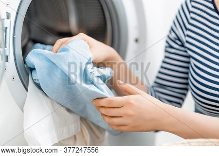 woman is doing laundry at home. laundry machine and hands close up