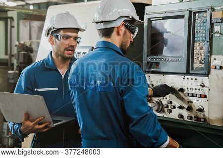 Mechanical  Engineer Or Worker With White Safety Helmet Checking On Production In A Factory. Industr