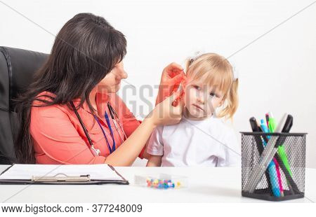 Cauacsian Doctor Otolaryngologist Examines The Ear Of A Little Girl Who Has Pain In Her Ear. The Con