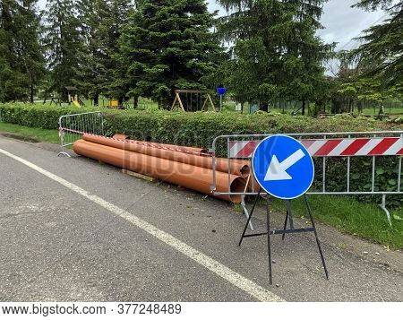 Road Traffic Sign And Pipes On The Asphalt Close-up. Constraction In Process