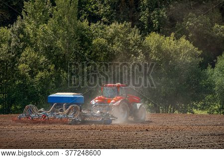 Modern Tractor In The Agricultural Field. Large Tractor Pulling Plow, Throwing Dust Up In The Air