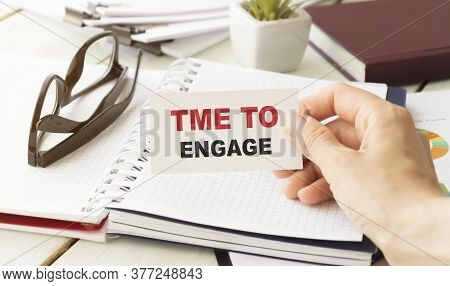 Text, The Word Time To Engage Is Written In A Notebook Lying On A Black Table With A Pen And A Cup O