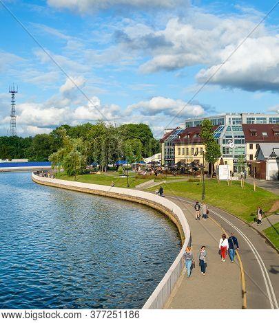Minsk, Belarus - July 17, 2019: People Walking By Svisloch River Embankment In Bright Sunny Daytime,