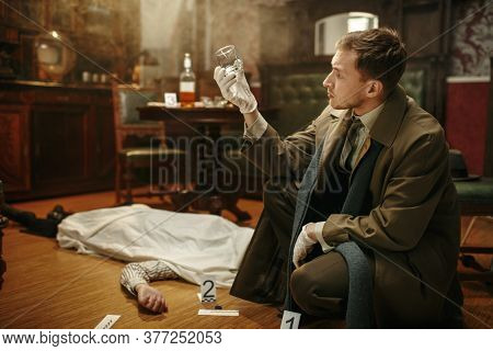 Male detective looking evidence at the crime scene