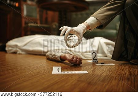 Detective with magnifying glass looking evidence