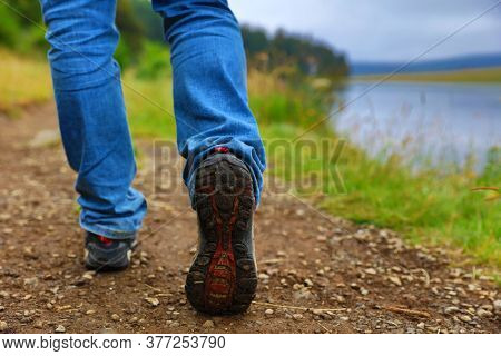 legs of lonely man wearing jeans walking along the path with lake- travel concept
