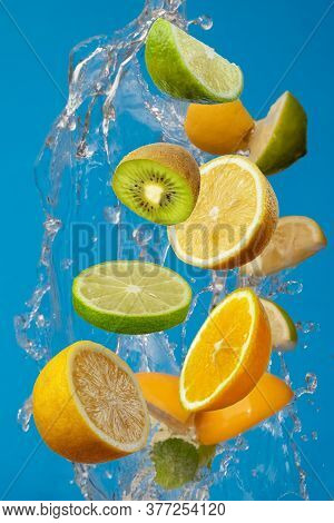 Falling Fresh Mixed Fruits. Slices Of The Lemon, Orange, Lime And Kiwi With Fresh Water In The Air.