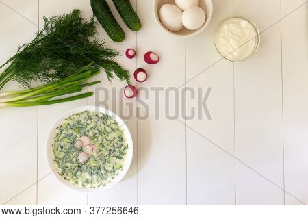 Cold Soup In A Deep White Plate With Ingredients On A White Table. Okroshka, A Traditional Dish Of R