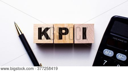 Kpi Is Written On Wooden Cubes Between A Pen And A Calculator On A Light Background. Business Concep