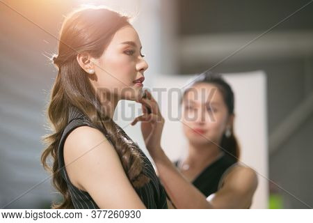 Selective Focus Of Happy Asian Model Actress Taking Brush On From Woman Make Up Artist Behind The Sc
