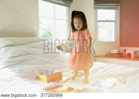 Portrait Of Adorable Asian Toddler Girl Stomping And Dancing Joyfully On The Bed While Listening To