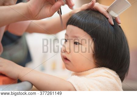 Portrait Of Cute Asian Toddler Girl Had A Hair Cut By Mother During The Covid-19 Coronavirus Pandemi