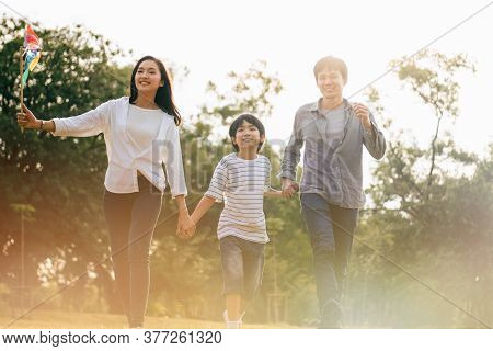 Scene Of Asian Happy Family Spend Time Together Walking And Relaxing At The Park In The Afternoon Au