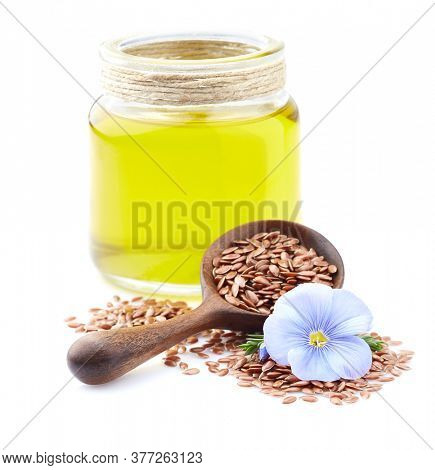 Flax oil with flax seeds in closeup on white