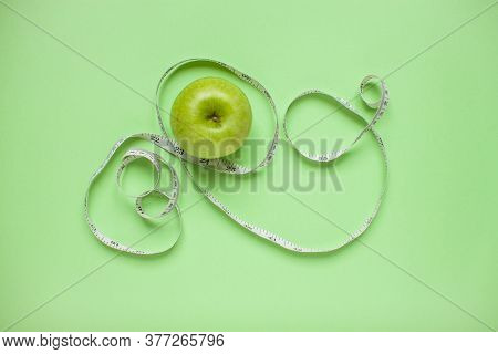 Diet And Healthy Eating Concept. Top View Of Weightloss. Green Apple And Measuring Tape. Green Backg