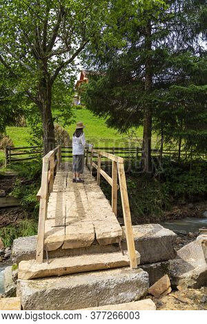 Woman - Hiker On  Wooden Pedestrian Bridge Through A Mountain River. Summer Holidays In The Carpathi