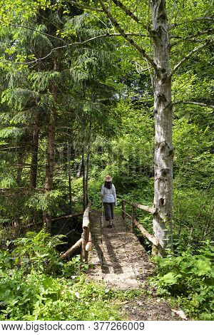 Summer Holidays In The Carpathian Mountains. Ukraine. Woman - Hiker On  Wooden Footbridge In Green C
