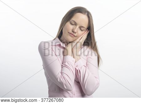 Young Caucasian Woman Pretending To Sleep Resting Her Head On Her Hands With Her Eyes Closed In Pink