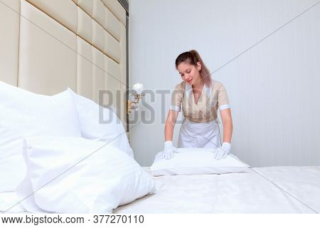 The Maid Straightens The Pillow After Changing The Bed Linen.the Concept Of Cleaning And Hospitality