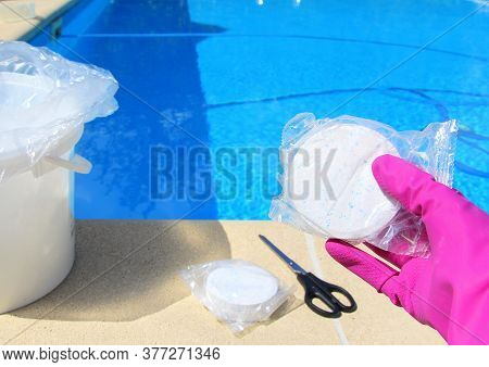 White Big Chlorine Tablet In The Hand Of A Service Worker For Disinfection Of Swimming Pools. The Be