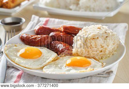 filipino silog breakfast with garlic fried rice, longsilog, and two sunny side up eggs
