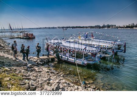 Luxor, Egypt - Jan 28, 2020: Touristis enter in boats on the Nile river in Luxor city, Egypt