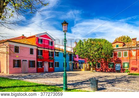 Colorful Houses Of Burano Island. Multicolored Buildings In Small Cobblestone Square, Blue Sky Backg