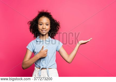 Smiling Cute Curly African American Kid Pointing With Hand Aside And Showing Thumb Up Isolated On Pi