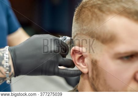 Visiting Barbershop. Close Up Shot Of A Young Caucasian Man Getting Trendy Haircut. Barber Using Pro