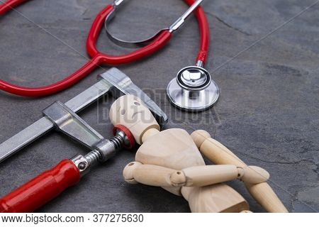 Image Shows A Wooden Puppet With Clamp And Stethoscope