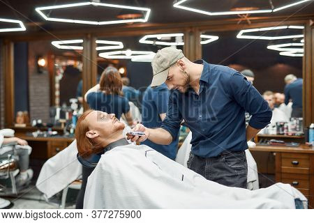Serving Client In Barbershop. Young Redhead Guy Sitting In Barbershop Chair And Getting Trendy Beard