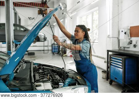 Young African American Woman, Professional Female Mechanic Opening Car Hood For Checking Car Engine