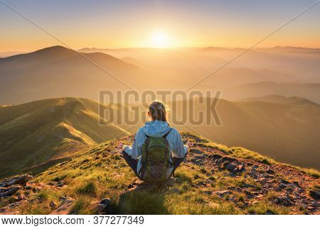 Young Woman With Backpack Sitting On The Mountain Peak And Beautiful Mountains In Fog At Sunset In S