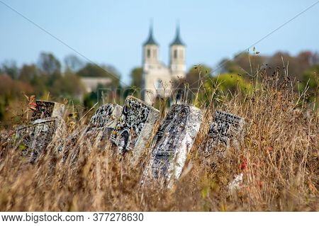 Old Jewish Cemetery In The Fall. Tombstones On A Background Of Dry Grass In A Cemetery. The Jewish C