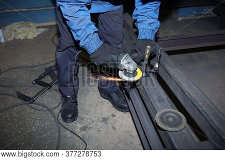 Grinding Metal.grinding Wheel. Locksmith Cleans Iron Corner After Welding In Workshop.