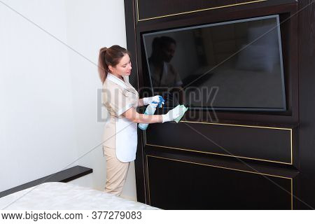 A Uniformed Maid Wipes The Tv In The Bedroom.room Service At The Hotel. The Concept Of Cleaning And